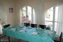 De eettafel in de ruime veranda waarin ook nog een tweezit en een driezitzetel staan.