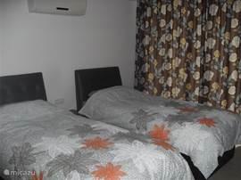 Vlak naast de badkamer ligt deze slaapkamer met 2 bedden en een ruime garderobe-kast.