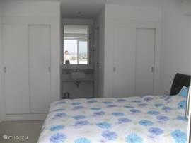 De andere slaapkamer heeft een 2-persoonsbed en 2 inbouwkasten. Daar achter bevindt zich de en-suite badkamer met wastafel (in het midden), toilet (rechts) en inloopdouche (links).