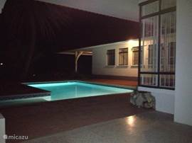 The pool is illuminated at night with the porch at the front of the villa.