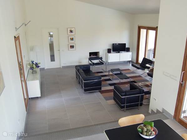 De woonkamer is een grote hoge moderne ruimte voor 8 personen.