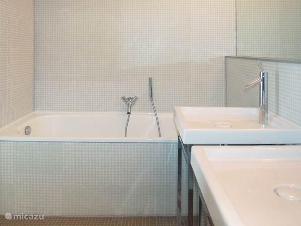 Een ligbad, een douche en een dubbele wastafel in de hoofdbadkamer.