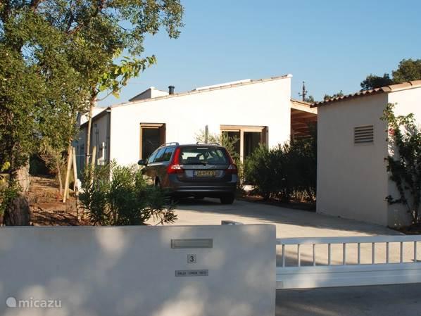 De entree met de ruime parkeerplaats. De villa ligt aan een doodlopende weg in een rustige buurt tegen de natuur aan, op 5-6 minuten lopen van Plage de Villata
