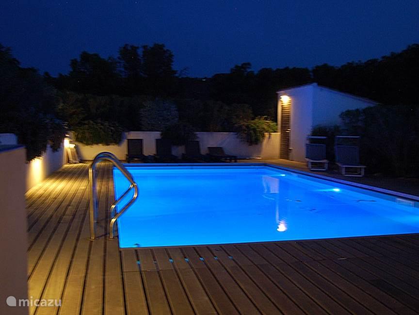 Het zwembad in de avond. De tuin, het zwembad  en de veranda zijn verlicht. Er zijn heel veel verschillende mogelijkheden om het zwembad te verlichten.