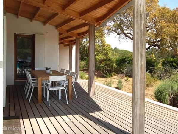 U kunt onder de veranda schaduw vinden aan de grote houten tafel met acht stoelen
