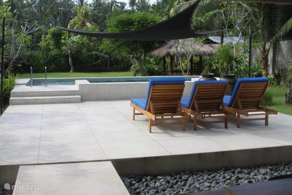 Terras bij zwembad met zonnezeil boven de ligstoelen