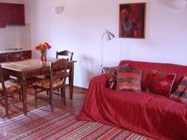 De woon/eetkamer is ingericht met warme kleuren en antieke houten meubels.