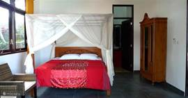 One of the bedrooms with four-poster bed, mosquito net, air conditioning and ample closet space.