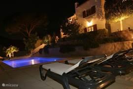 Het huis/zwembad in de avond.