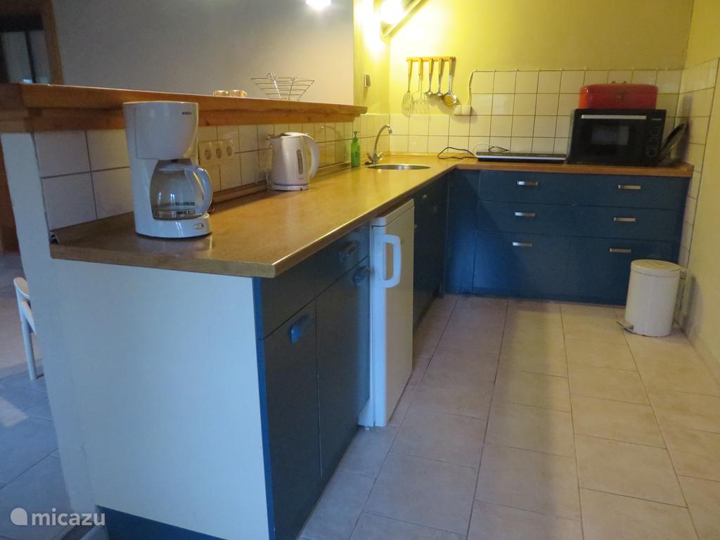 Open keuken, met koffiezetapparaat, waterkoker, oven en 2-pits inductie kookplaat