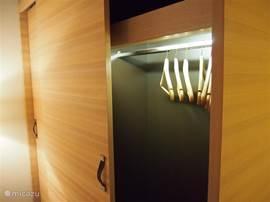 Hoogwaardig afgewerkte inbouw kledingkasten met verlichting in de slaapkamer.