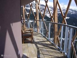 Een groots op het zuiden gelegen balkon met ligstoelen is te betreden vanuit de woonkamer en vanuit de slaapkamer en biedt groots uitzicht over de bergen.