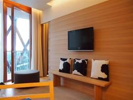 Vanuit de woonkamer en slaapkamer met uitzicht op de bergen kun je rechtstreeks het grote ronde balkon betreden. Het appartement, geheel met hout en in-bouwkasten afgewerkt is een loft waarbij alle ruimten met elkaar in verbinding staan via schuifdeuren. Veel indirecte verlichting zorgt voor sfeer.