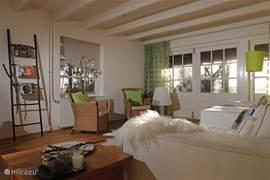 Gezellige woonkamer in het geusthouse met veranda en uitzicht over de landerijen