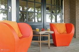 Zitje op veranda bij guesthouse, geniet van de stilte en kijk uit over de weilanden