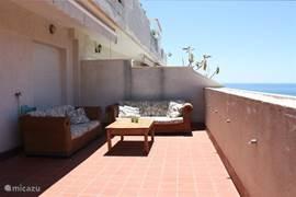 Een lounge set op het balkon met uitzicht over de zee