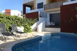Backyard with patio, pool, deck chairs