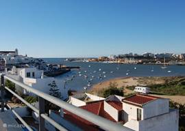 One of the most beautiful views in the Algarve Ferragudo with fishing boats, the mouth of the Arade river and marina of Portimao