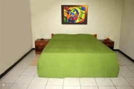 slaapkamer met een 2persoonbed met gezondheidsmatras en kussens, nachtkastjes, schilderij