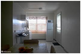 keuken met kasten,eet en ontbijtborden,bestek,potten en pannen,elektrische kookstel,koelkast,magnetron,keukenlinnen,koffieset apparaat,fluitketel