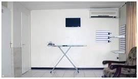 in de slaapkamer bevindt zich een strijkplank met strijkbout,hang en legplanken voor de kleding,flatscreen tv,airco,zitbank