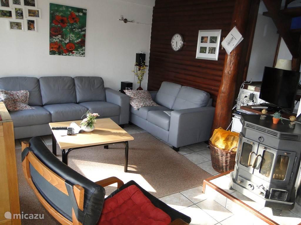 In de woonkamer staat o.a. een leren bankstel,en een gezellige houtkachel