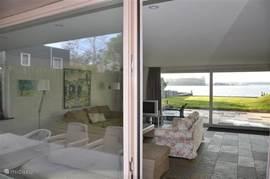 Doorkijk vanaf het terras voor het huis door de woonkamer naar het terras en tuin grenzend aan het Veerse Meer.