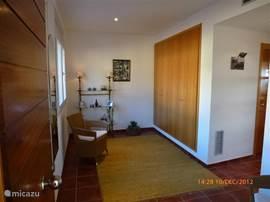De entree heeft een ruime hal met extra kastruimte voor garderobe. Naar rechts gaand, ( zie onderstaande foto) de gang naar de woonkamer.