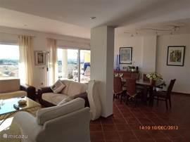 Het rechterdeel van de woonkamer met nog een eetkamertafel en 6 stoelen. Rechts achterin de deur naar het terras. De woonkamer heeft het gemak van 'n aircondition.