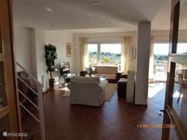 Een heel grote lichte woonkamer waarvan u hier de helft ziet. Een plavuizen vloer geven een gemakkelijk onderhoud en een gezellige sfeer. Links de leuning van het trappenhuis naar de bovenverdieping voor de drie slaapkamers.