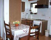 Kitchen with microwave, stove and refrigerator. Dining area.