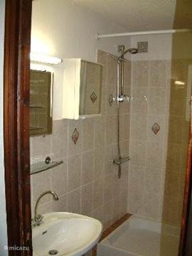 badkmaer with shower and sink, toilet in a separate room