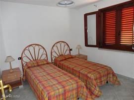 Slaapkamer met 2 eenpersoonsbedden en openslaande ramen