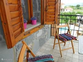 Op de 1e etage aan de eetkeuken ontbijt terrasje met stoelen en tafeltje.