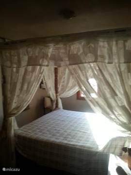 Op de 1e etage bevindt zich een ruime slaapkamer met king size hemelbed en garderobe kast.