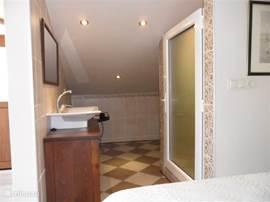 Badkamer bij de slaapkamer op de 2e etage met douche, toilet en vaste wastafel ook hier voldoende handdoeken.