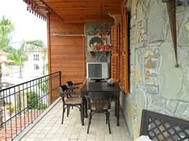 Terras 1e verdieping aan de woonkamer met uitzicht op de prachtige tuin en zwembad voorzien van eetafel