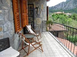 Terras 1e etage aan de woonkamer met mooie relax stoelen om rustig te genieten.