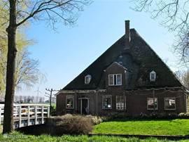 Onze originele stolpboerderij uit 1890 is rondom gelegen in het water.