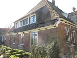 De zijkant van de woning met Engelse rozentuin en op  de bovenverdieping de kinderslaapkamers.