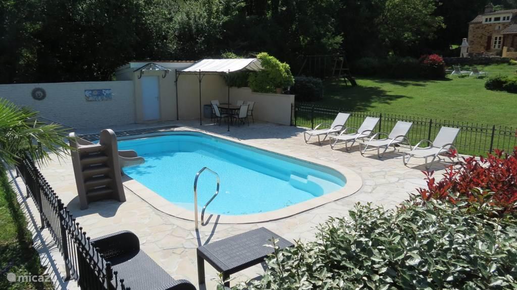 zwembad, buitendouche en water glijbaan, witte deur geeft toegang tot de sauna ruimte