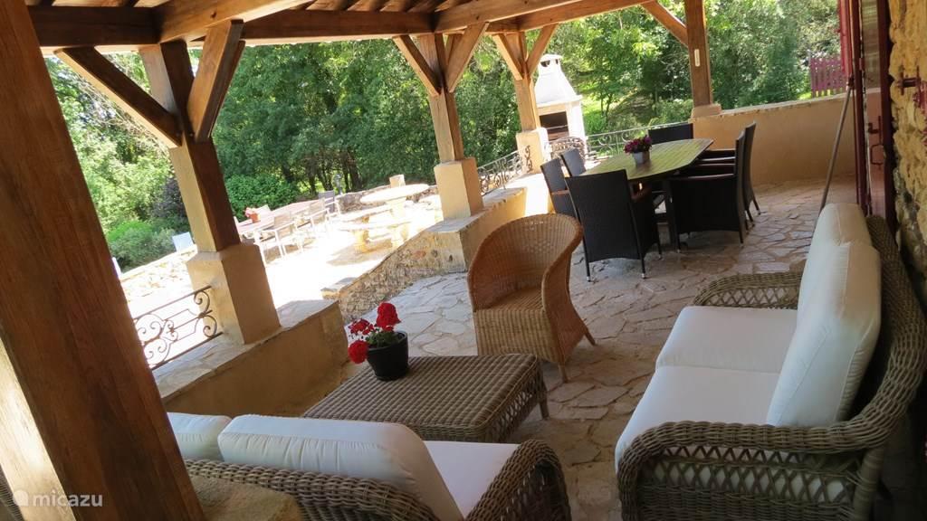 Terras met zitje en grote tafel. Op de achtergrond de stenen BBQ. Draadloos internet ook op de terrassen.