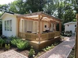 Het vakantiehuisje met overdekte veranda en tuindeuren. Er zijn 2 slp kamers. In het schuurtje staat o.a. een fiets en een laden vrieskast. Er zijn voldoende stoelen (bijv. loungeset/verstelbare tuinstoelen/ligbedden) en zon en schaduwplekken.
