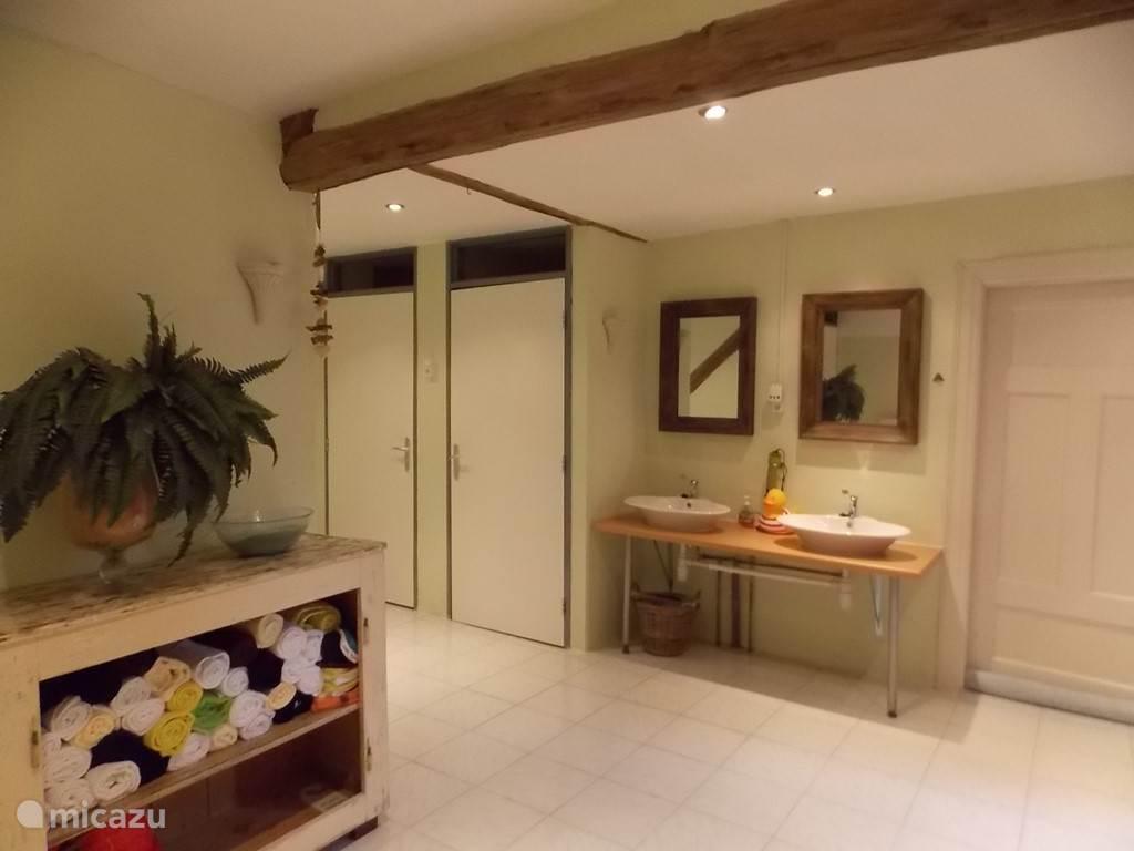 De grote douchruimte met 2 apparte toiletten en 2 apparte ruimtes met een douche en wastafel