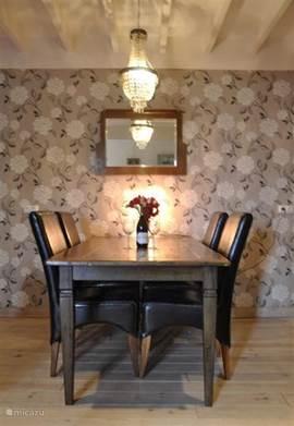 Ook in de woonkamer staat nog een eettafel met 4 stoelen.