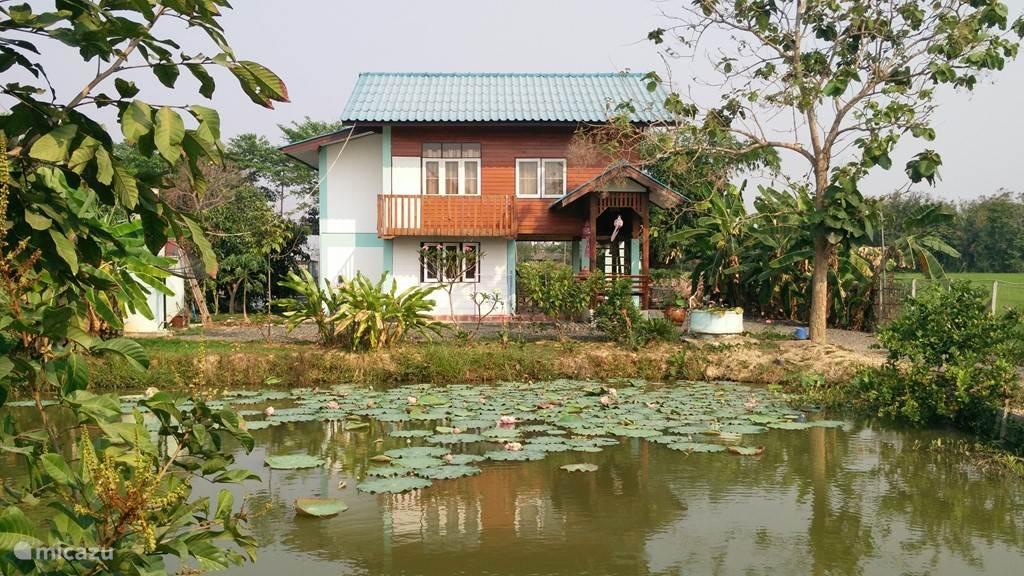 Teakhouten huis gezien over de vis vijver