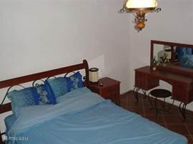 Slaapkamer met openslaande deuren naar het terras naast het huis.