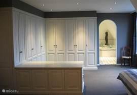 De walk-in closet met daarachter de badkamer