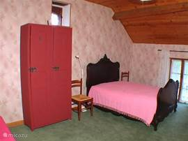 Bedroom 2 is a spacious room with the bed next to one another 2 single beds with garden views.