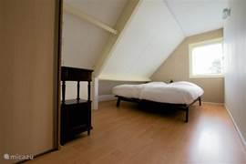 Slaapkamer 2, van 19m2 met een tweepersoons bed van Auping. Eveneens met ingebouwde hangkasten.